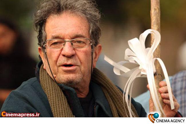 داریوش مهرجویی کارگردان سینمای ایران در پشت صحنه نارنجی پوش